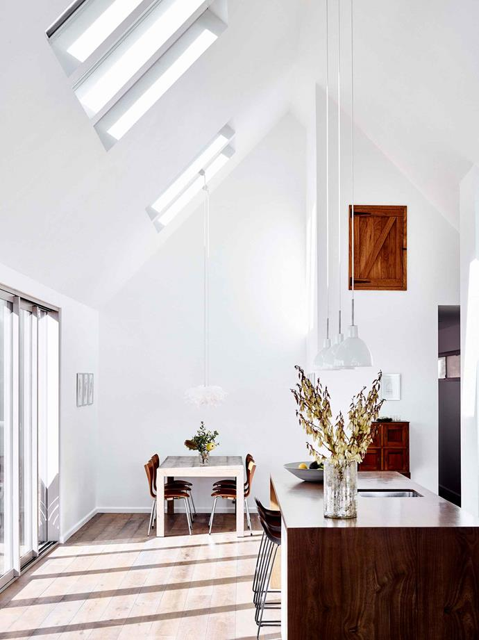 """The open-plan kitchen and dining area is flooded with natural light, thanks to an abundance of skylights. [Louis Poulsen](https://www.louispoulsen.com/