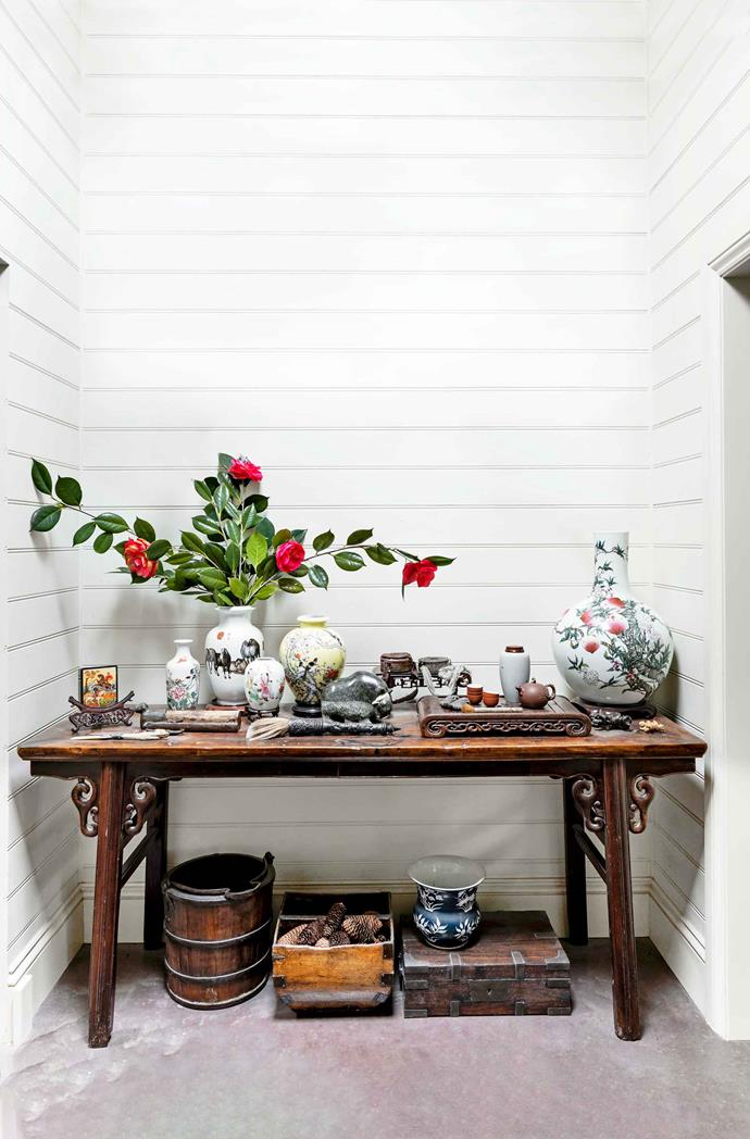 Camellias from the garden grace a Chinese altar table displaying antiques and souvenirs.