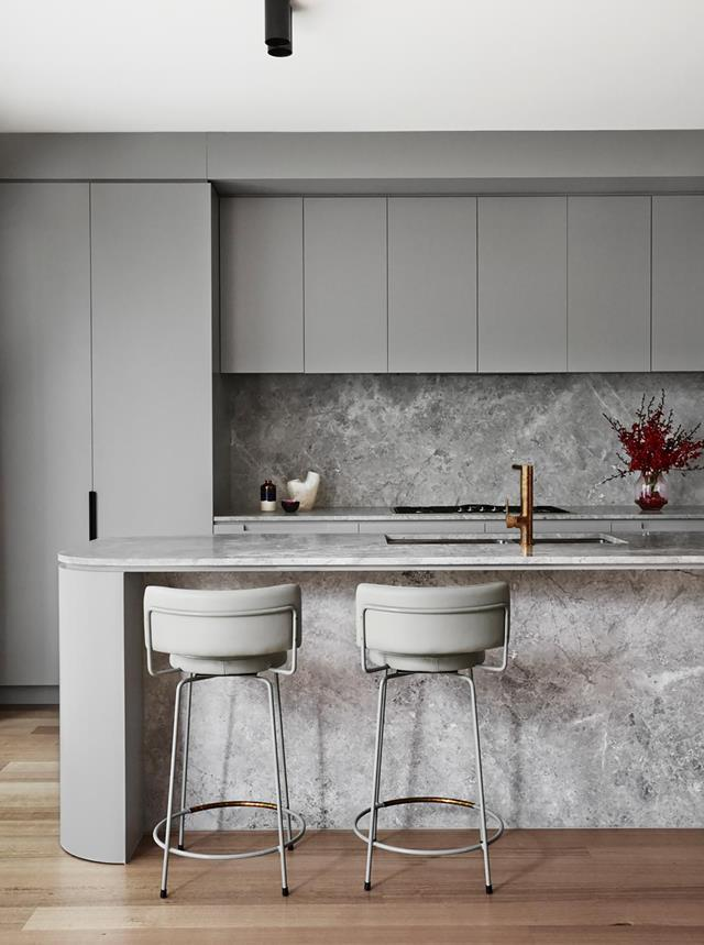 """Soft grey curved cabinetry and natural stone benchtops has been pared with light timber floors in this [high-end pad's](https://www.homestolove.com.au/high-end-pad-in-south-yarra-19733
