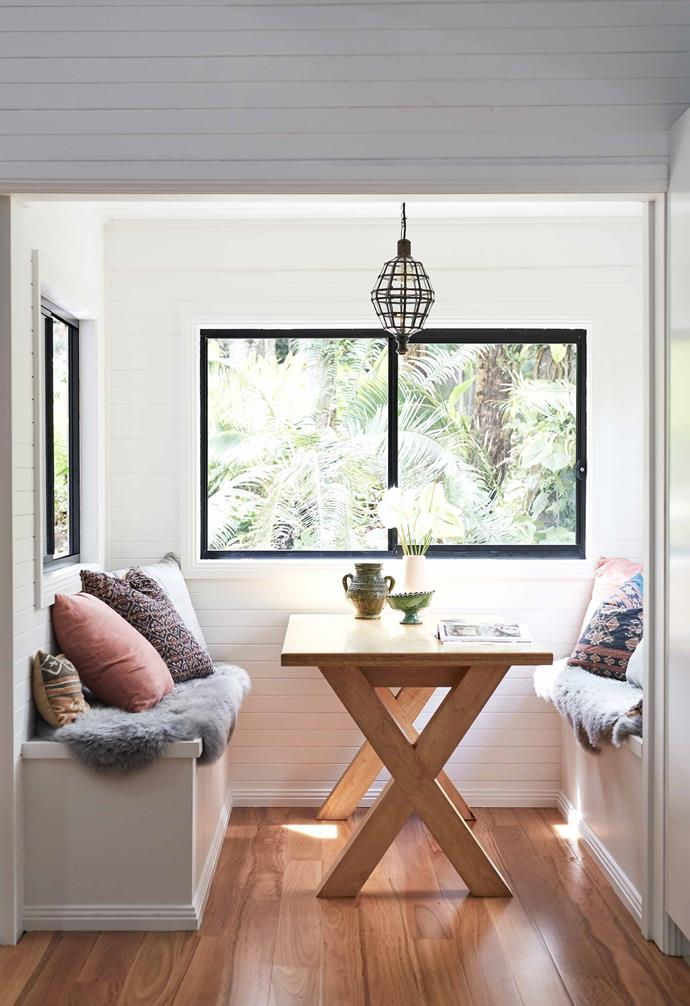 """**Dining nook** Lush palms and ferns are framed by the black-edged windows. Mikarla had storage benches made to fit snugly on either side of the [Habitat Home Collection](http://www.habitathomecollection.com.au/