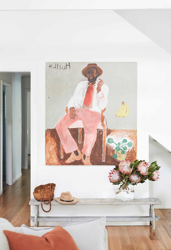 """**Living area** On the staircase side of the room, the upbeat pastel shades of Emma Gale's artwork The Hustle are picked up in a stunning display of proteas. Replica Eames white table, [Matt Blatt](https://www.mattblatt.com.au/