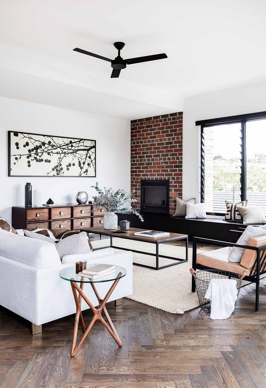 The furniture in this cosy living room is orientated toward both the brick fireplace and the louvre windows.