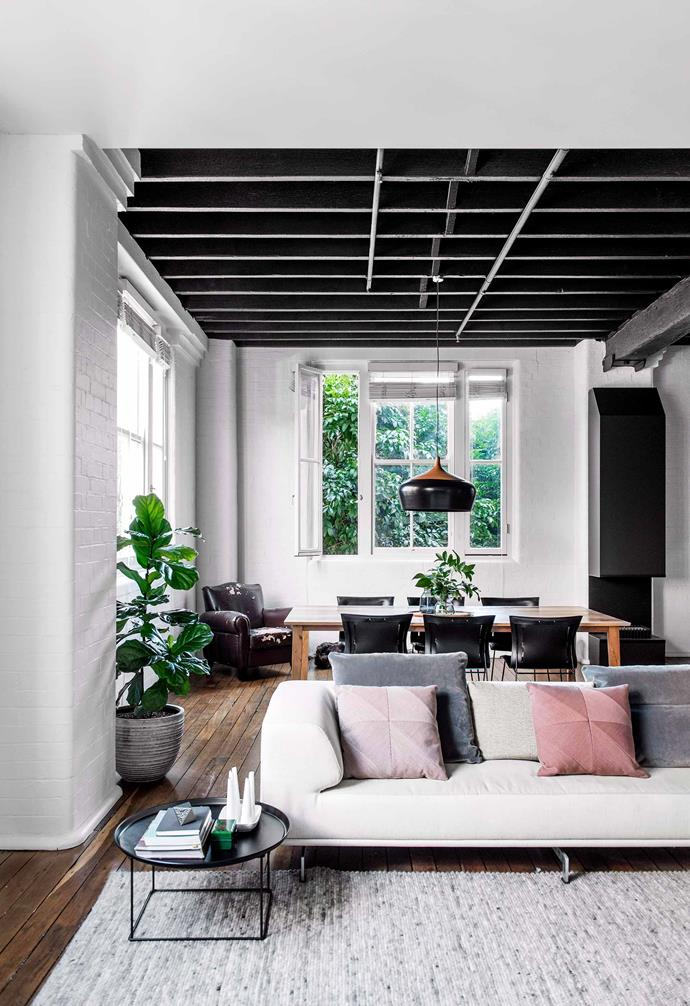 This loft-style home in Brisbane features an open-plan layout with the neutral rug creating a loose separation of spaces.
