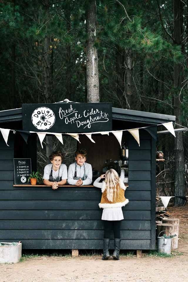 """Twins Harry and Bertie Showers run their own apple cider donuts business from this black weatherboard cubby house on their apple orchard and farm, [Black Barn Farm](https://www.homestolove.com.au/black-barn-farm-20518