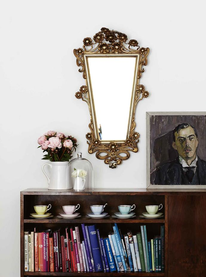 Annabelle loves mixing and matching — Royal Albert teacups and a 1950s European oil portrait share the early modern Danish walnut bookcase near the 19th-century French mirror.