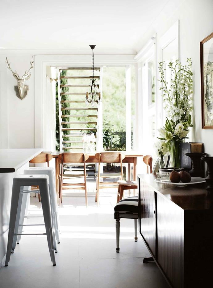"""A 19th-century French chandelier hangs above the 1960s Danish teak dining table, while the stag's head sculpture is from local homewares store [Living by Design](https://livingbydesign.net.au/