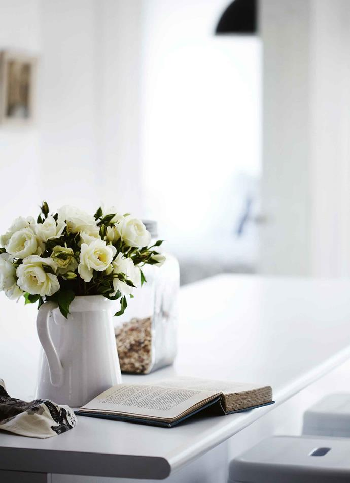 Home-grown roses fill a jug on the kitchen bench.