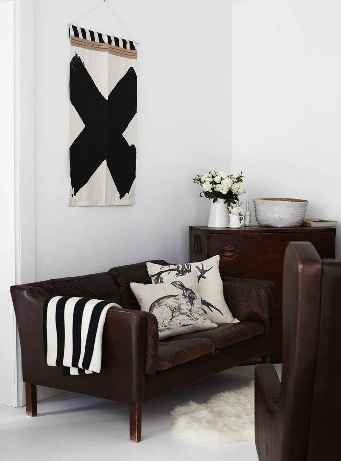 """In the living room, roses offset the dark furniture. The wall-hanging and antler cushion are from Australian homewares designer [Pony Rider](https://www.ponyrider.com.au/