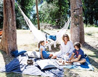 Family picnic outdoors with hammock in the background