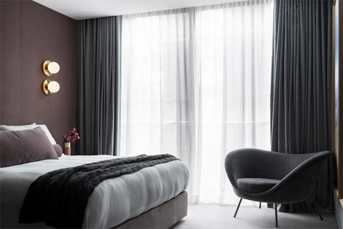 Custom bed, cushions and upholstered wall panels, all by Nina Maya Interiors, with 'Line' wall lights by Douglas and Bec, and linen and cashmere throw from Bemboka. Molteni&C armchair by Gio Ponti against silk and linen curtains by Lovelight.