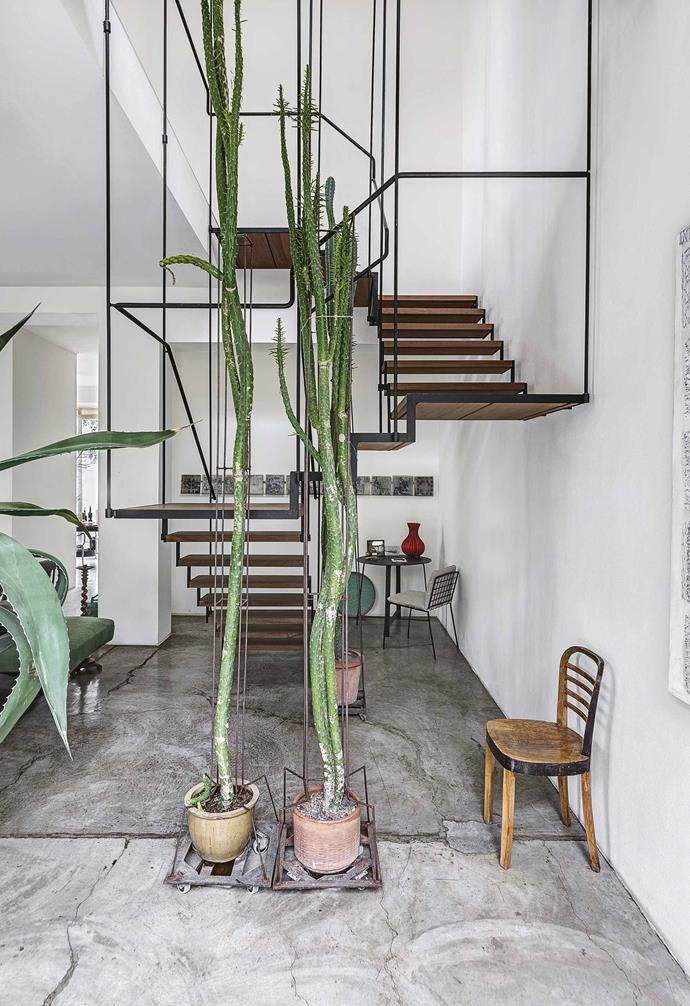 "The last point is important because the home doubles as Antonino's work space, where he creates metal sculptures and objects. ""My favourite spot in the house is the studio, which is also a showroom, and is always open to customers and curious people,"" he says.<br><br>**Staircase** The custom stairs, designed by Antonino, are a work of art in their own right. Draw attention to high ceilings and voids with huge plants. Oversized greenery throughout the home draws a playful connection between ideas of scale and height."