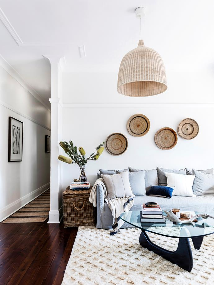 **Living room:** A collection of woven baskets on the living room wall is a nice alternative to a single piece of art. A wicker pendant and chest, which serves as both storage and side table, complete the look.