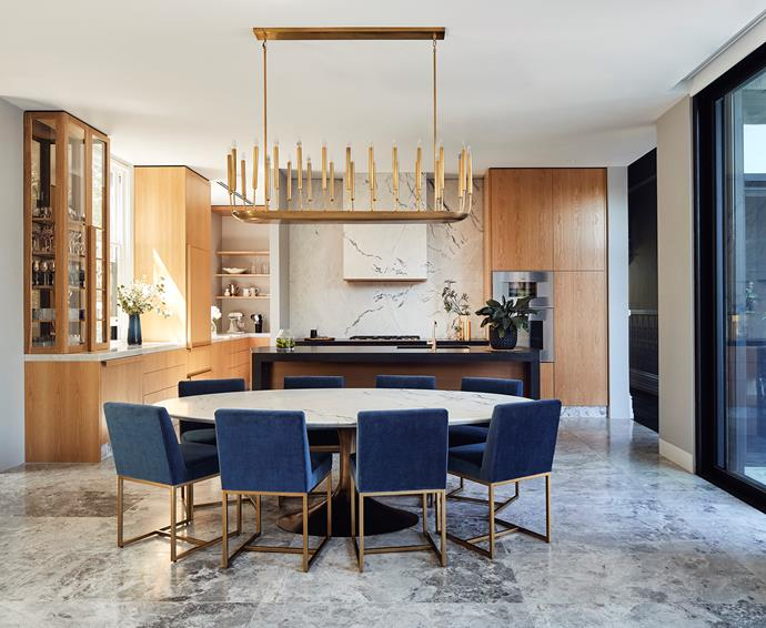The open plan kitchen and dining space features a marble table top that was custom made by Parthenon Marble. Ovens are Wolf.