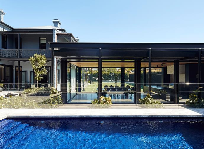The pool house is flanked by a sleek swimming pool and tennis court.