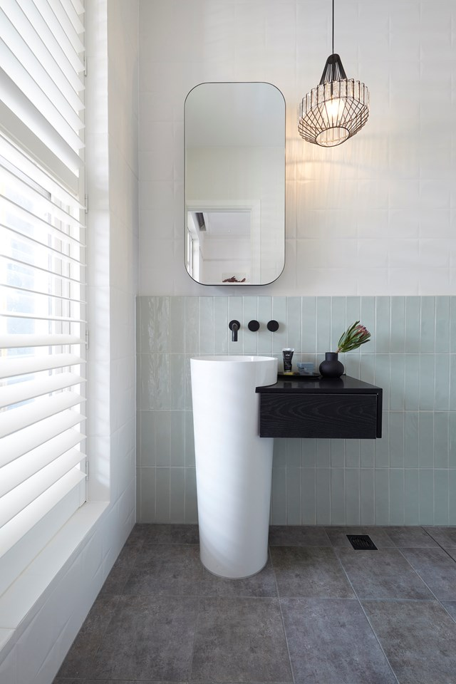 Concrete floor tiles are softened by handmade, sage green subway tiles in Elise and Matt's ensuite.