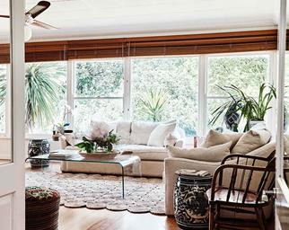 Bright sunroom with sofas, jute rug and wooden blinds