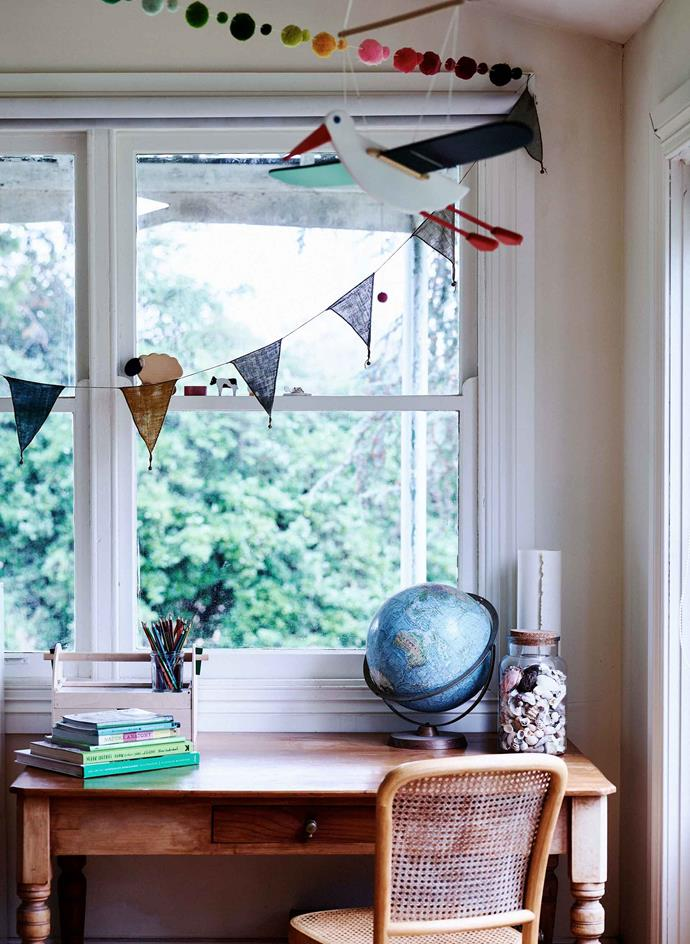 A vintage desk decorated with bunting flags. The globe is a family heirloom.
