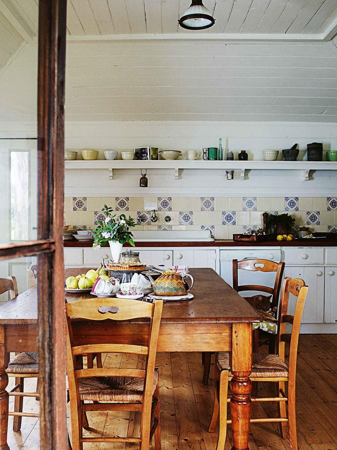 "The kauri timber for the kitchen floor ""came from an old shearing shed up the road"". The kitchen, and specifically its fireplace, is the heart of this home. ""That old fireplace is almost as high as us when we stand,"" she says. ""It's got a big cast-iron arm where we can put a pot on. And quite often — because in the winter that fire in the kitchen goes 24/7 — we just cook on the fire. Sometimes lamb cutlets, or there's a big pot where we cook our casseroles, our stews."""
