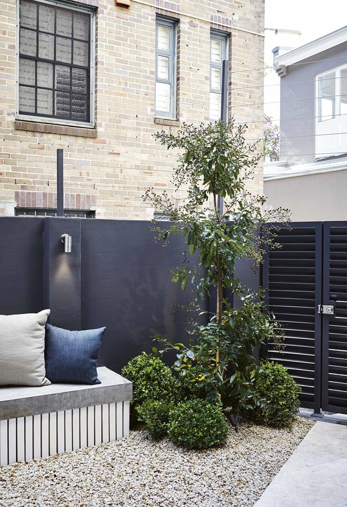 """What works here is the tonal similarity between the travertine stone, gravel and concrete with interplays of texture. The area feels spacious and has enough detail to be interesting without being fussy. <br><br>**Back garden** A variety of textures creates different zones in this narrow garden. Cushions from [Eco Outdoor](https://www.ecooutdoor.com.au/