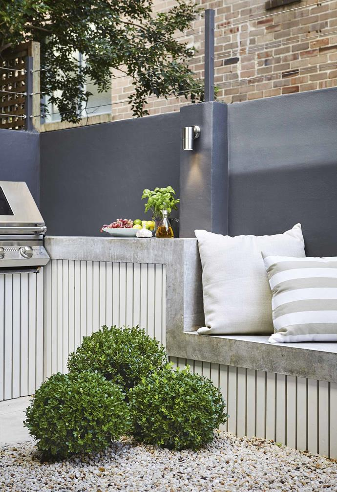 """Another key in a small space is using a high-impact element – here, it's the concrete bench. It stretches along the wall for ample seating then morphs into the taller benchtop, which houses the built-in barbecue. The sleek shape and finish emphasises a crispness, evident in the other surfaces. """"It's a challenge to get the most out of an area without overwhelming the space,"""" says Phil.<br><br>**Back garden and barbecue area** Lighting by [Gardens At Night](https://www.gan.com.au/