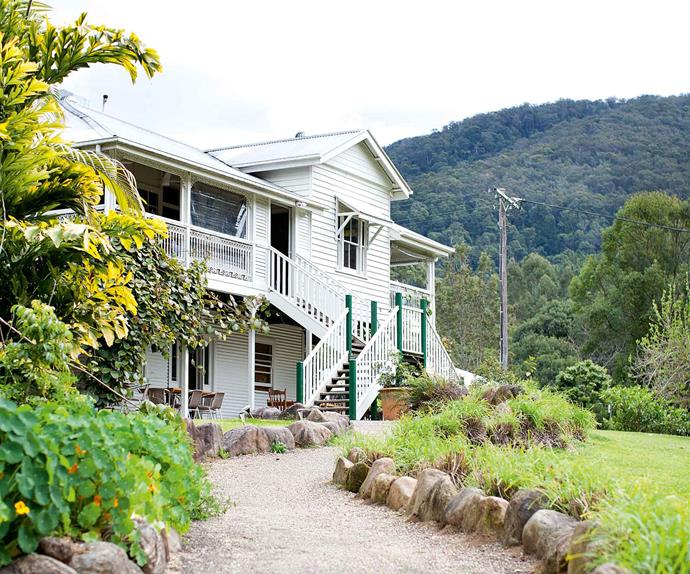 Weatherboard Queenslander home with mountains in background
