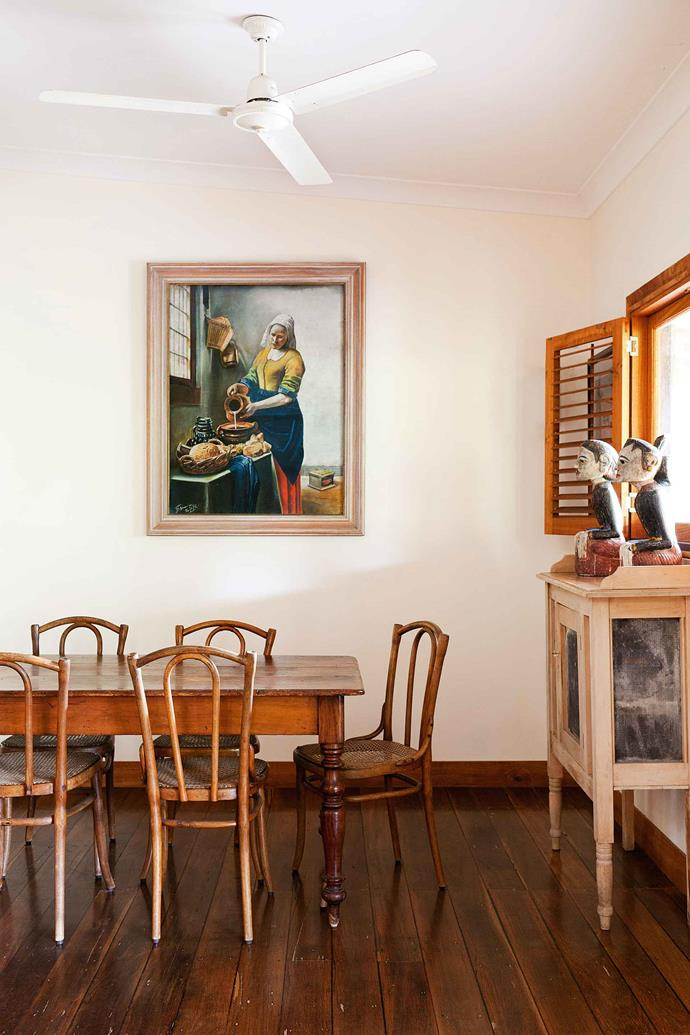 In the dining area of the guest farmhouse, carved Javanese heads look out towards  a copy of Vermeer's famous The Kitchen Maid.