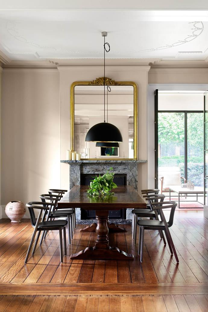 "In this [Georgian-style home's](https://www.homestolove.com.au/stone-love-georgian-style-home-gets-some-tlc-2030|target=""_blank"") formal dining room, an antique table is juxtaposed with contemporary Kiki seating from MCM House. The large Catellani & Smith pendant light is an unexpected addition, yet creates an elegant synergy with the gilt mirror above the Victorian marble fireplace. From *Belle* October 2015."