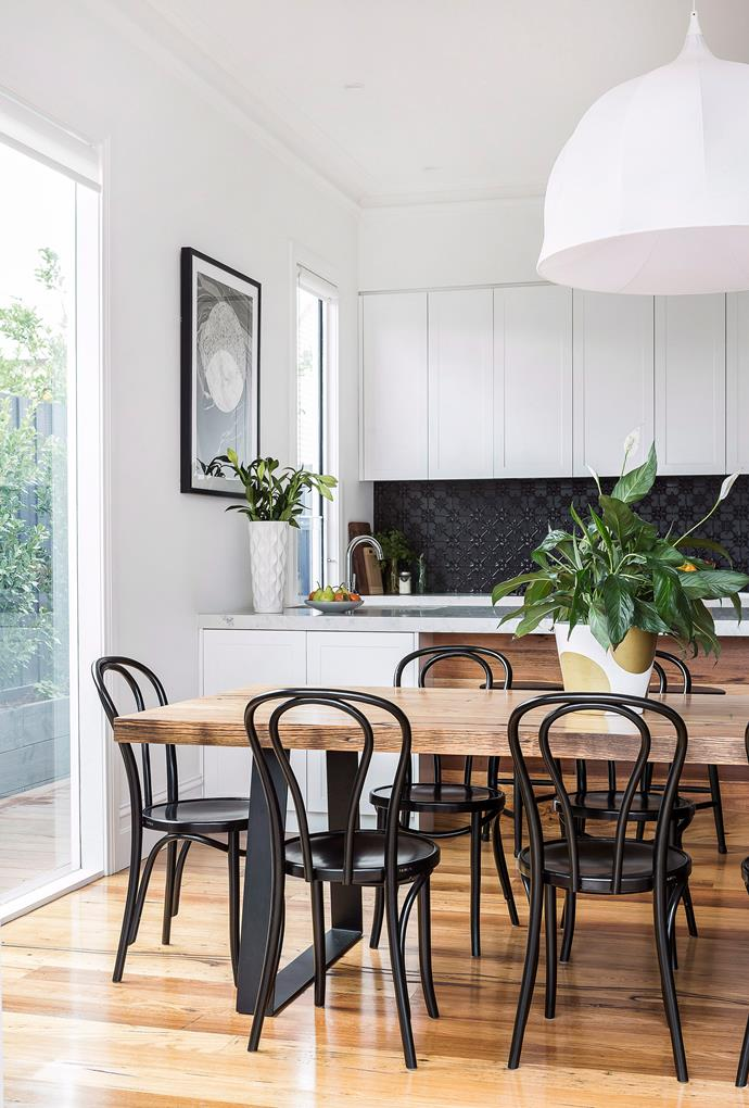 Classic black Bentwood dining chairs tie in with the legs of this timber dining table creating a cohesive look.