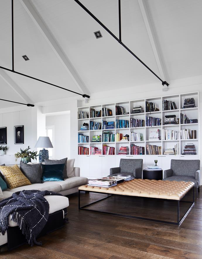 Custom-made cube shelves attest to Troy's love of books, which have been subtly colour coded in this collection. Black steel cross-struts support the vaulted V-groove ceilings.