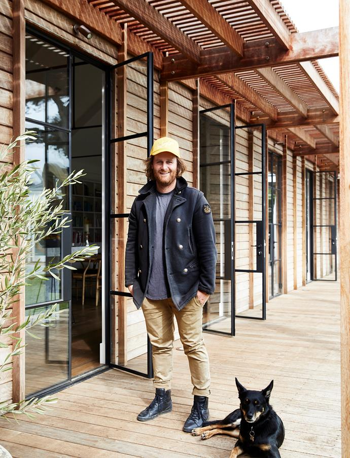 Troy Robinson and his kelpie, Roo, on the verandah, which features stylish slatted pergolas.