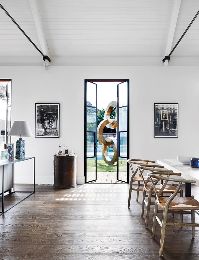 Luna dining table, MCM House. Framed limited-edition prints by Natalie Nowotarski flank the steel-framed doors that open out to the courtyard and outdoor entertainment area with its striking steel sculpture, United by Lachlan Ross.