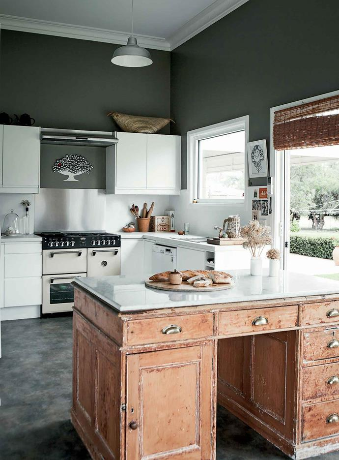 The kitchen cabinet was bought at auction, half stripped and topped with marble.