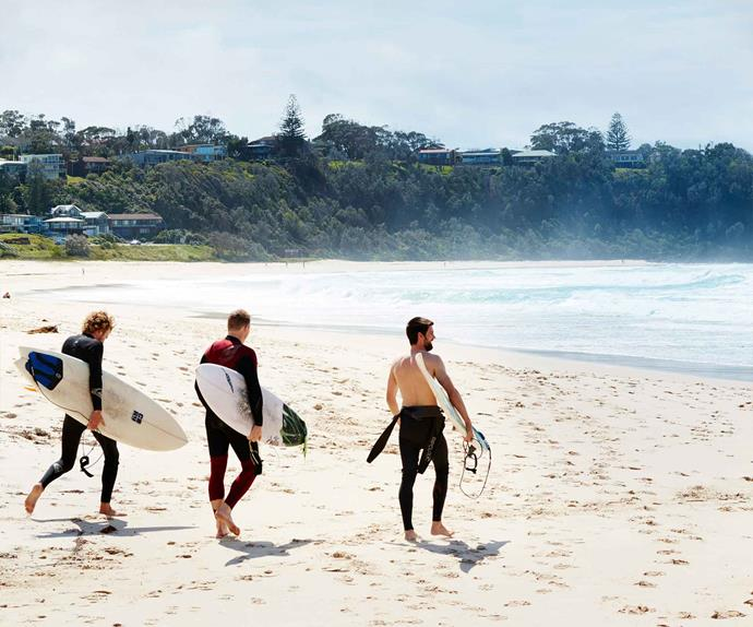 Three surfers on a beach in Mollymook, NSW