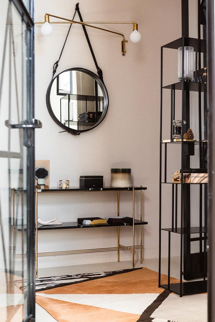 Laure's signature style becomes apparent as soon as you enter her home, from the doors, which she had made from steel and glass, to the sleek open shelving by GamFratesi. The round mirror is a Jacques Adnet design for Gubi, the lamps are by Bloomingville and the carpet is from La Redoute.