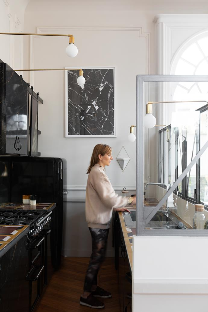 """My favourite room is the kitchen, where I created a structure to divide the space without separating it,"" Laure tells. The Bloomingville lamps are a modern take on Art Deco style. Angular wall sconces and decorative tiles on the kitchen countertops also draw inspiration from this timeless design decade."