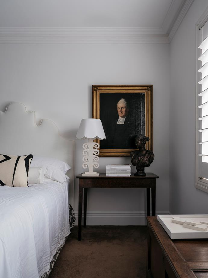 Previously wallpapered in a dark grey pattern to match an upholstered bed, the bedroom walls are now crisp white. The new bedhead design echoes the lamps, both Phoebe's creations. They're a modern contrast to the antique bedside table and painting.
