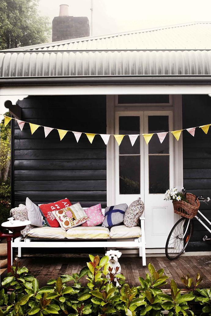 The exterior of the house is painted in Taubmans Black Fox. Maltese Hugo in front of a day bed whose cushions Jane Frosh has covered with recycled tea towels and other vintage fabrics.