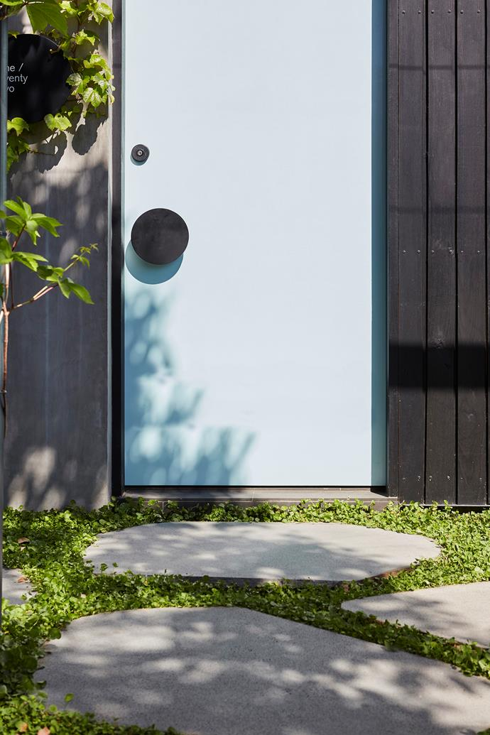 Permeable natural bluestone steppers lead up to the light blue front door, a signature shade of the owner-architect's.