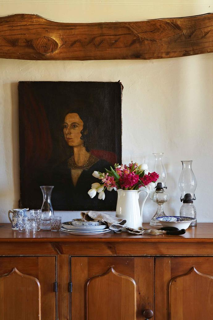 An unsigned portrait from the 1860s sits above an antique sideboard in the dining room.