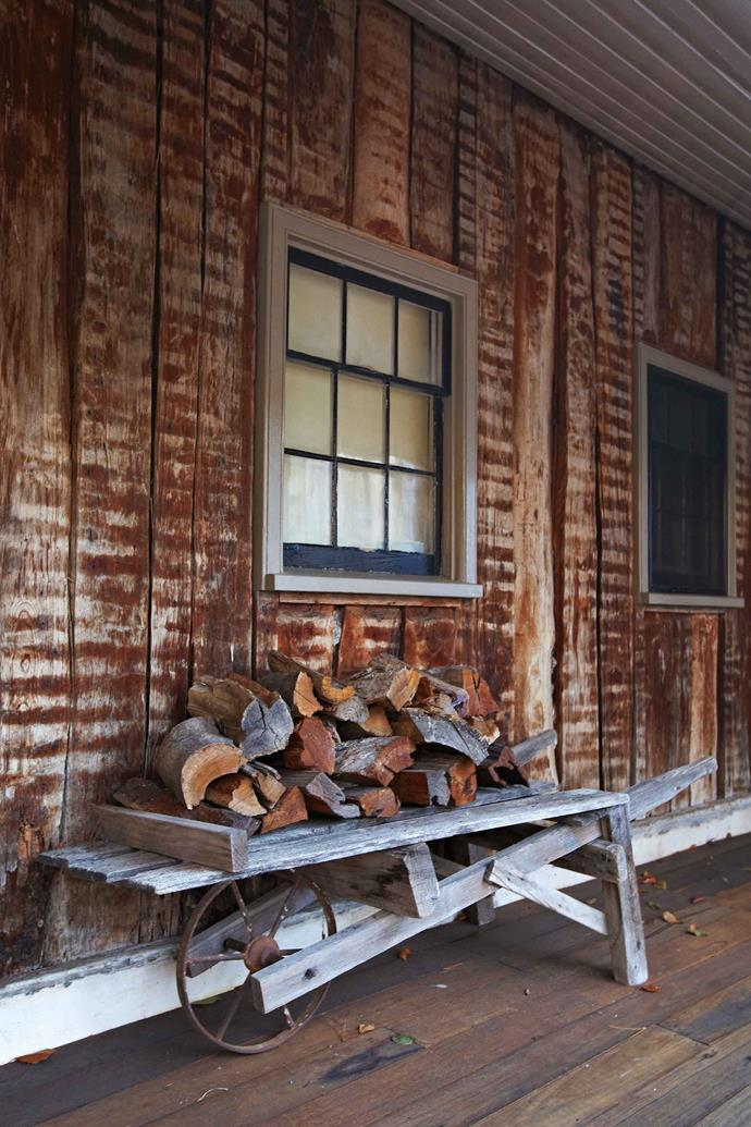A store of firewood is piled by a slab-built section of the house.