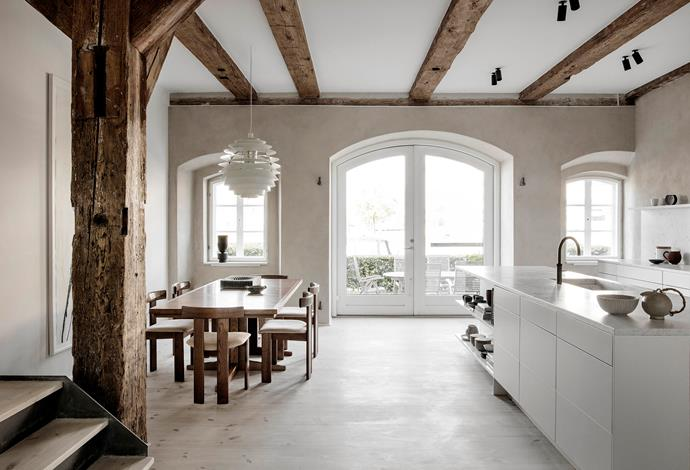 Large arched windows and doors connect the open-plan kitchen and dining zone with the garden, and provide uninterrupted views of the canal. The sleek kitchen island is honed Carrara marble.