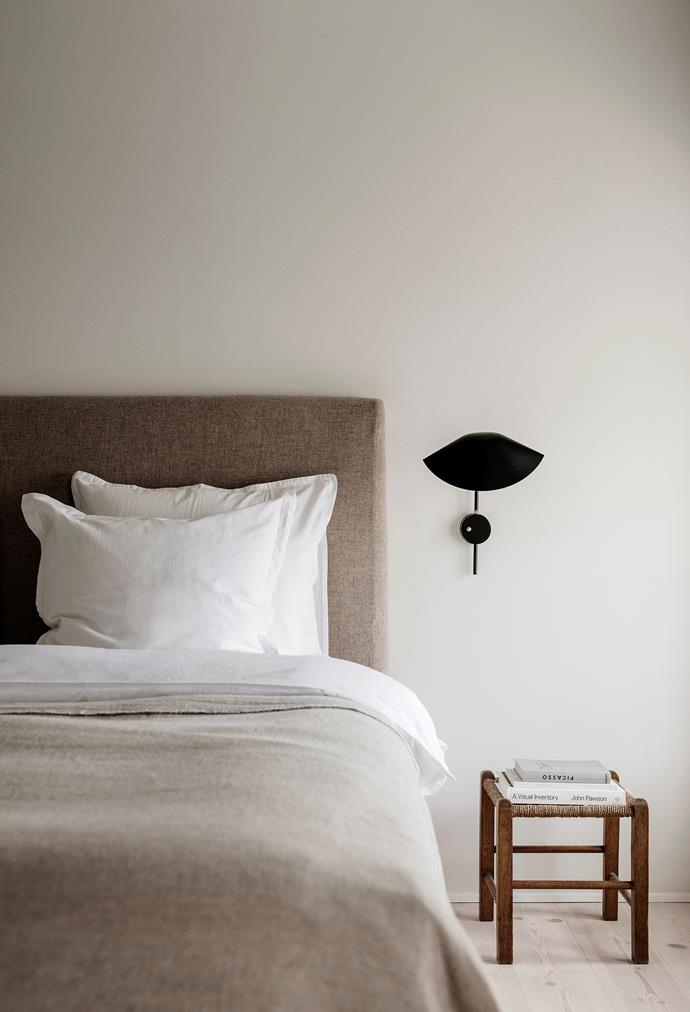The master bedroom is calm and soothing thanks to a material bedhead, touchy-feely bedlinen and restrained colour palette. A black and brass Serge Mouille wall lamp adds just the right amount of drama.