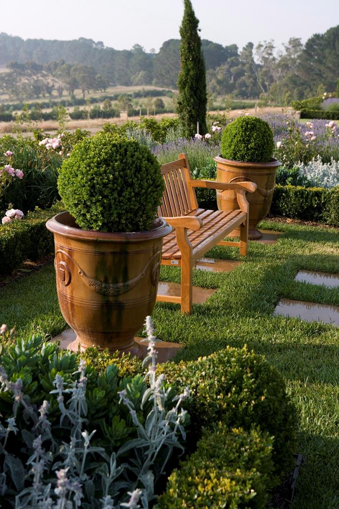 Two potted topiary balls help to zone this seating area while creating symmetry.