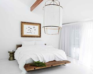 Clean, all-white bedroom with oversized linen pendant
