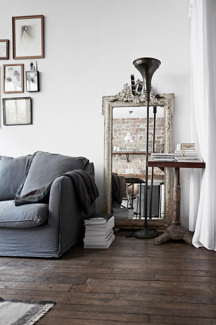 A beautifully arranged corner creates stillness in a busy,  multi-purpose space. The lamp is an heirloom and the ornate mirror and side table are antique finds.