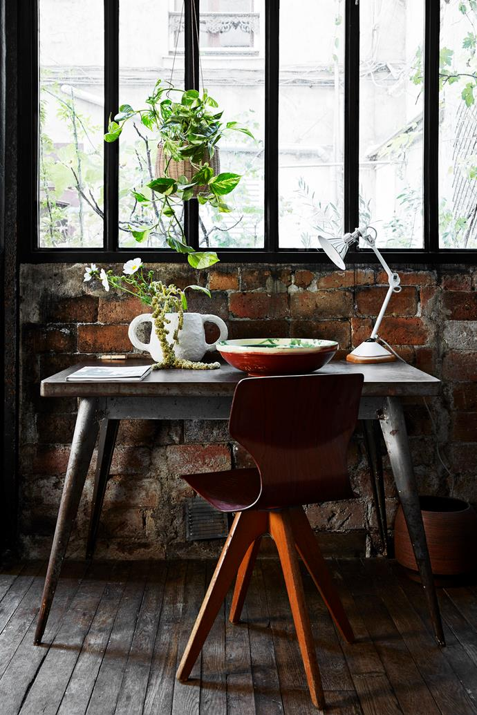An iron Tolix table from a flea market in Nice gets plenty of sun beneath this window – and so do the indoor plants. As evening falls, light is provided by the DWC éditions 'Lampe Gras' lamp. The curved  chair is from a store in Paris called Le Plus de Design.