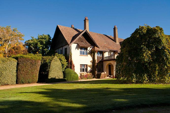 A giant weeping elm and the striking tapestry hedge frame the Arts and Crafts-style homestead.