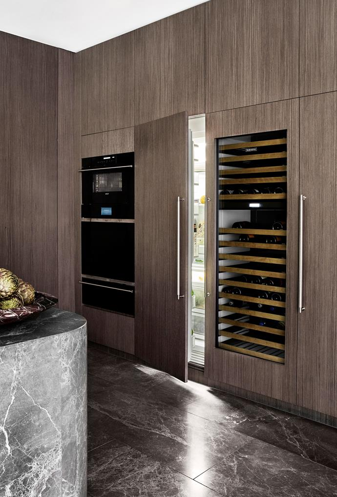 Dark timber veneer in 'Essential Metro' from Eveneer and Buster + Punch handles. Oven 'ICBCSO30CM/B' M Series Contemporary single oven, Contemporary convection steam oven and 'ICBWWD300' warming drawer in Black Glass, all from Wolf. Refrigerator/freezer 'ICBIC-30FI' column freezer with ice maker, 'ICBIC-30RID' column refrigerator with internal dispenser and ICBIW-30 wine storage, all from Sub-Zero