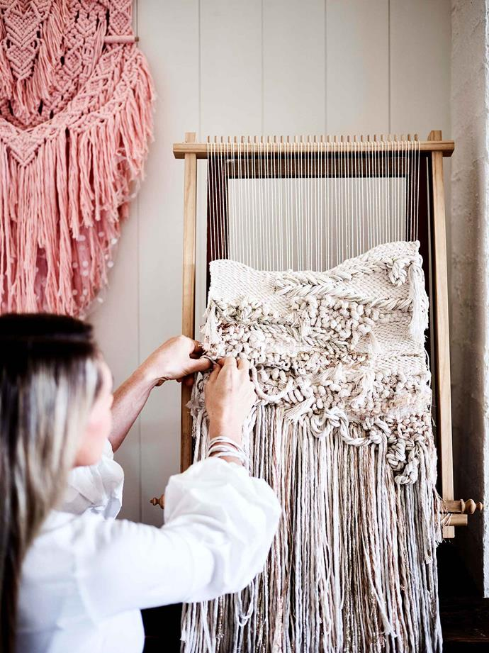 Working on a wall-hanging, the fringing of which can weigh up to six kilograms.