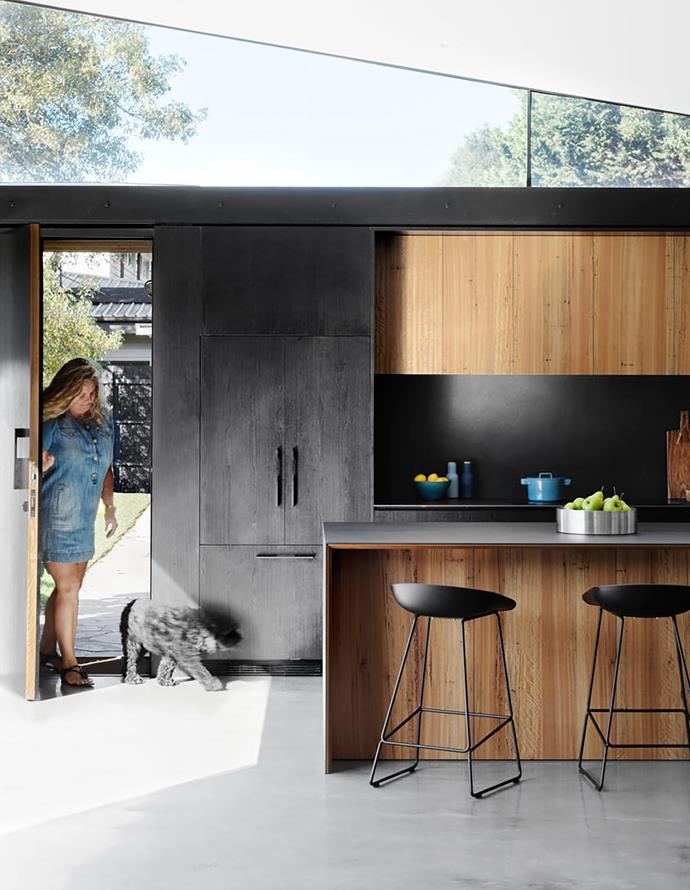 Samantha and her spoodle Charlie enter via the front door, which opens directly into the kitchen. The dark joinery, in Eveneer 'Ravenna' timber veneer, is balanced by the use of blackbutt for the surrounding cabinetry. The striking benchtop is made from Maximum Moon pressed porcelain from Artedomus.